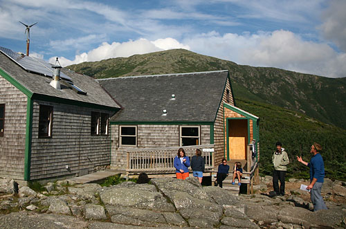 Helon Hoffer 08 (right) gives a green-tech tour to hikers outside the Greenleaf hut.