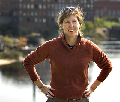 Lynne Lewis stands on the Auburn side of the Androscoggin River with the former Cowan Mill, in Lewiston, in the background.
