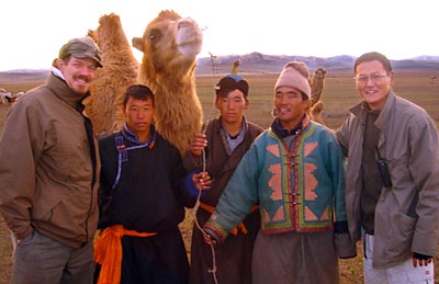 Gil Crawford (left) visits Mongolia in 2004 to conduct due diligence on a microfinance institution, XAC Bank. At right is bank CEO Ganhuyag Ch.Hutagt; in middle are MFI clients. MicroVest made its initial investment in XAC, of $1.5 million, a few months later and has continued to provide financial capital since then.