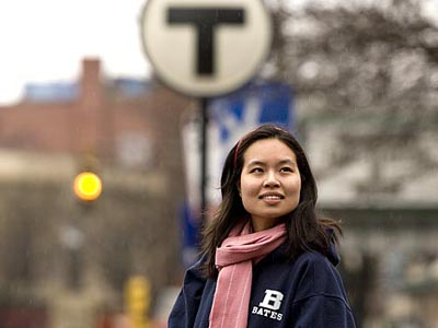 Somerville is an incubator for young alums adjusting to the real world, says Swita Charansomboon 04, standing in Davis Square near a familiar mass-transit symbol. Photograph by Phyllis Graber Jensen.