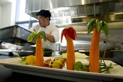 Thoune Thongsavanh works at the vegetarian-vegan station. (Phyllis Graber Jensen/Bates College)