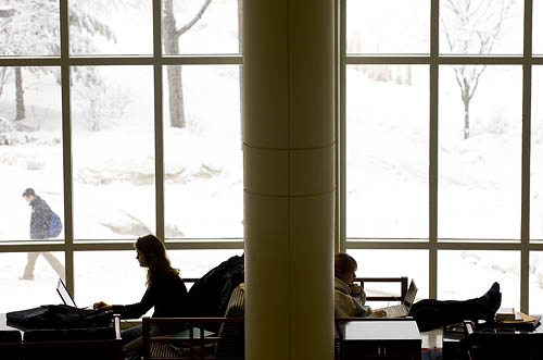 Students study in Pettengill Halls Perry Atrium as an early spring snow blankets the campus.