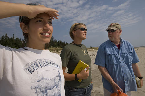 From left, geology thesis students Dana Oster 09 and Emily Chandler 09 work with Professor of Geology Mike Retelle to study climate-induced changes at Phippsburgs Seawall Beach.